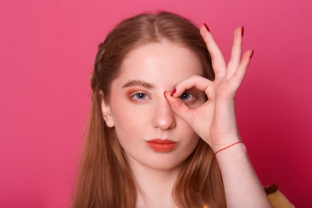 Serieuze jonge vrouw, maakt ok teken, tegens haar oog, drukt vertrouwen uit, model poseert op roze, fotograferen. mensen en gebaar concept.