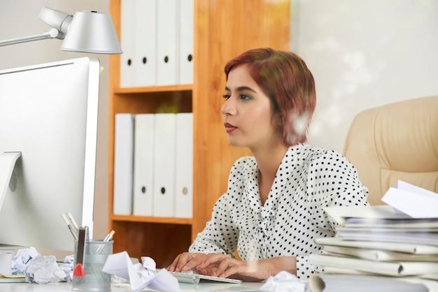 Serieuze jonge vrouwelijke ondernemer die e-mails van klanten en collega's op de computer beantwoordt