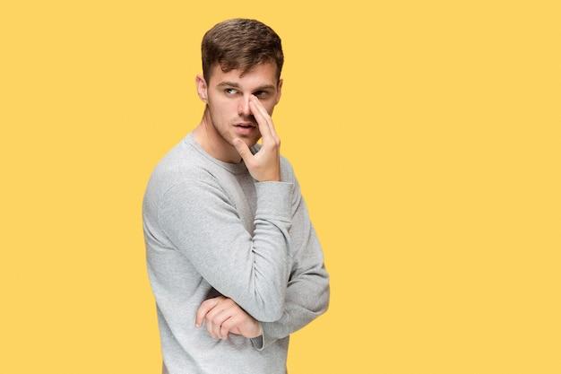 Serieuze jongeman voorzichtig kijken op gele studio achtergrond en spreekgeheim voor camera