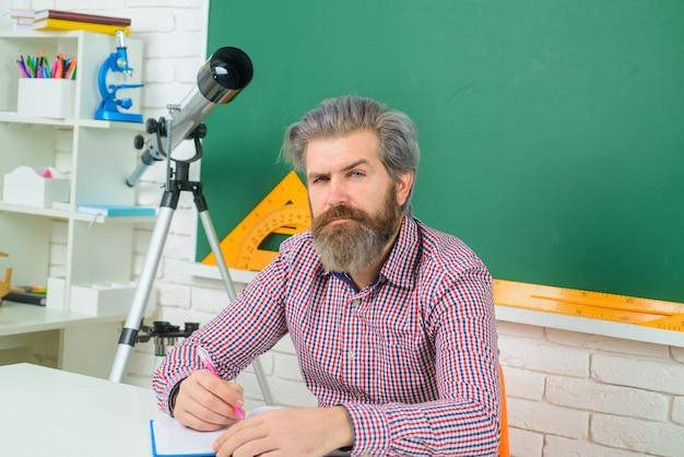 Serieuze leraar in klaslokaal leren onderwijs schoolconcept september leraar bereidt lessen voor in
