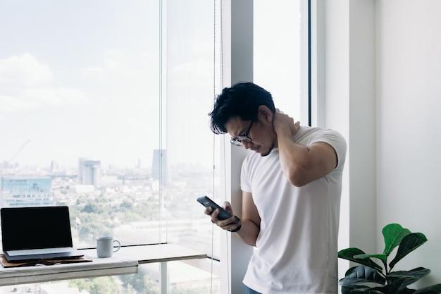 Serieuze man aan het werk met computer en telefoon met uitzicht op hoogbouw
