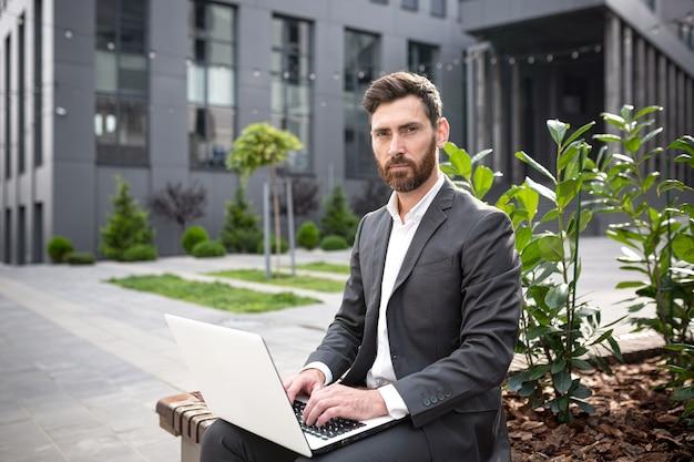 Serieuze man bankier die naar de camera kijkt terwijl hij op laptops werkt, tijdens de lunch, zelfverzekerde zakenman die in de buurt van kantoor zit