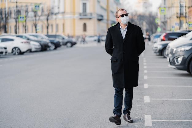 Serieuze man loopt op straat, gekleed in een elegante outfit, draagt een medisch masker om coronavirus of een ander type virus te voorkomen, blijft veilig tijdens de quarantainetijd. pandemische situatie