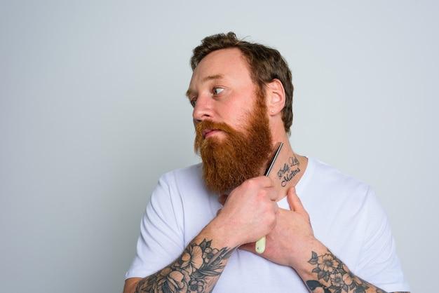 Serieuze man met mes is gefocust op het knippen van zijn baard