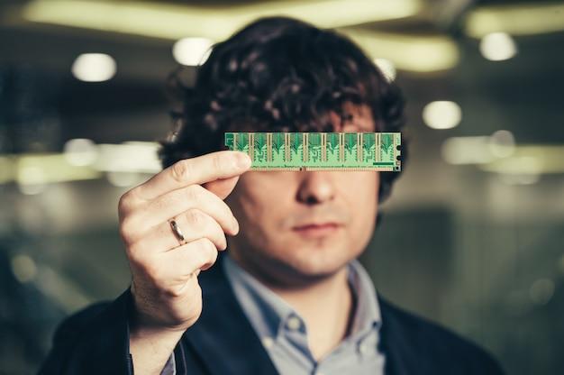 Serieuze man sloot hem de ogen met de microschakeling. ram in handen van een zakenman. anoniem verstopt achter de chip. werkgeheugen.