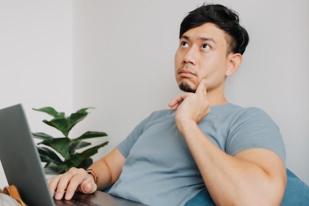 Serieuze man werkt op computerlaptop terwijl hij thuis blijft