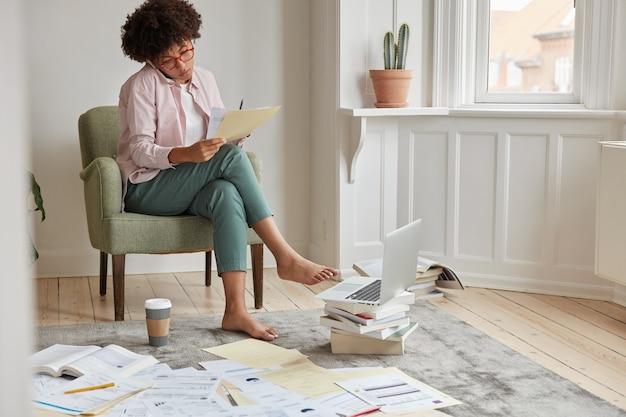 Serieuze manager leest documenten, analyseert informatiegegevens, zit in een comfortabele fauteuil Gratis Foto