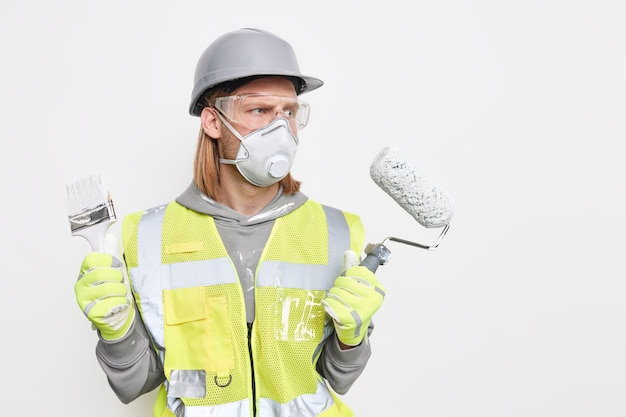 Serieuze mannelijke decorateur biedt professionele service houdt schilderrolborstel gebruikt gereedschap