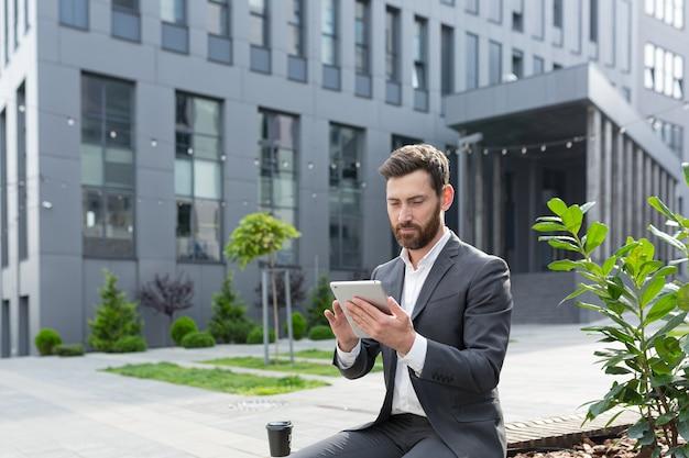Serieuze mannelijke freelancer in een pak die naar een online cursus kijkt, gebruikt een tablet, zittend op een openbare plaats op een bankje
