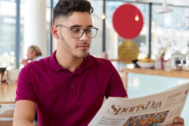 Serieuze mannelijke ondernemer begint de dag met een ochtendkrant, analyseert nieuws in de pers, draagt een optische bril voor goed zicht, draagt een casual t-shirt, concentreert zich op het lezen van een artikel in de cafetaria.