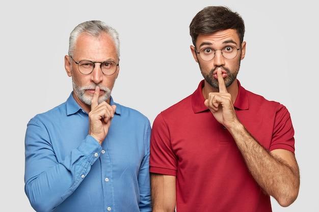 Serieuze mannen vertellen geheimen, maken een stil gebaar, raken de lippen aan met wijsvingers, staan naast elkaar tegen een witte muur. senior man in formele kleding brengt vrije tijd door met zoon, stiekem kijken