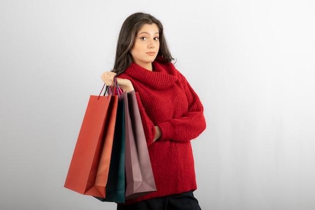 Serieuze meid houdt boodschappentassen vast.
