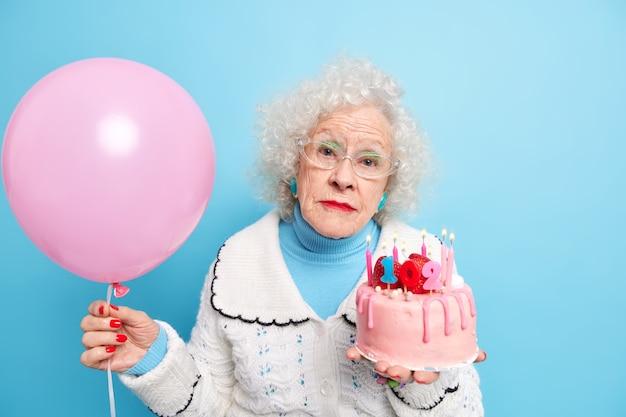 Serieuze modieuze oudere dame kijkt direct, viert verjaardagshoudingen met feestelijke cake en opgeblazen ballon die op pensioen is