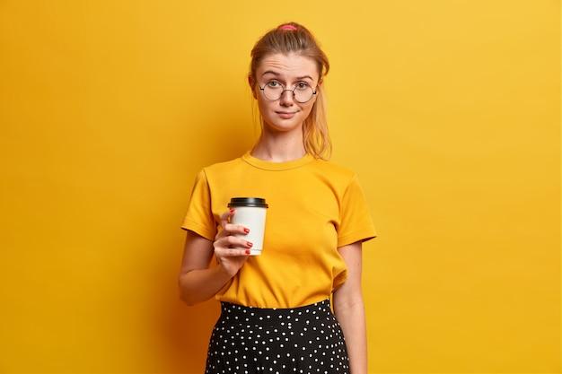 Serieuze mooie meid brengt vrije tijd door met nieuwe vriend houdt afhaalmaaltijden koffie drinkt drank en ziet er ongelukkig uit draagt gele t-shirt optische bril staat binnen