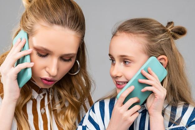 Serieuze mooie vrouw die een belangrijk telefoontje heeft terwijl ze bij haar zus blijft terwijl ze haar smartphone bij zich heeft