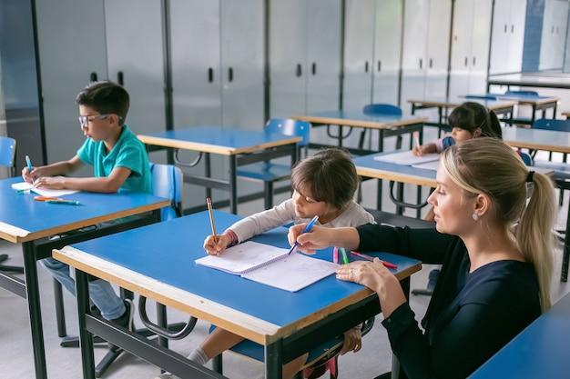 Serieuze onderwijzeres die leerlingen helpt om hun taak in de klas uit te voeren