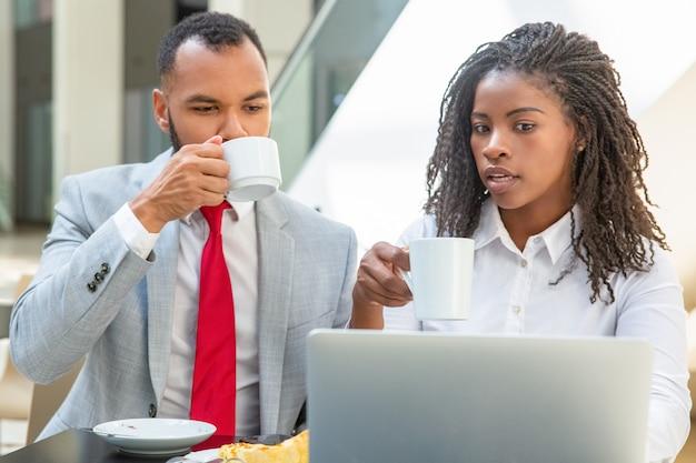 Serieuze professionals bespreken project tijdens koffiepauze