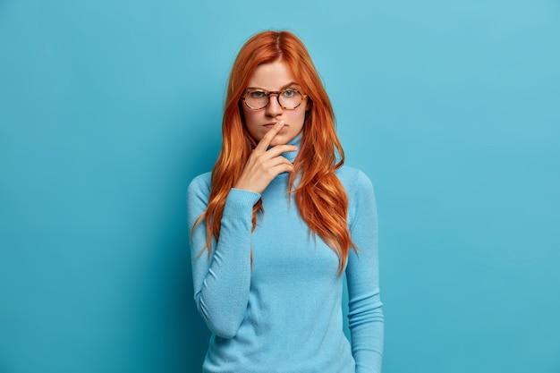 Serieuze rustige vrouw heeft natuurlijk lang rood haar houdt de handen op de lippen en kijkt met geconcentreerde, doordachte uitdrukking.