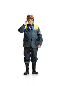 Serieuze senior bebaarde mannelijke mijnwerker staande op de camera met smartphone op een wit