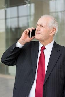 Serieuze senior business man wegkijken en bellen op smartphone