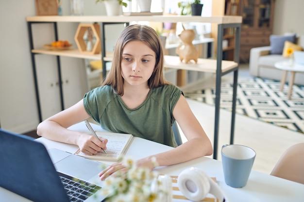 Serieuze tiener die naar laptopscherm kijkt terwijl hij deelneemt aan de bespreking van de opdracht tijdens online les en aantekeningen maakt in het schrijfboek