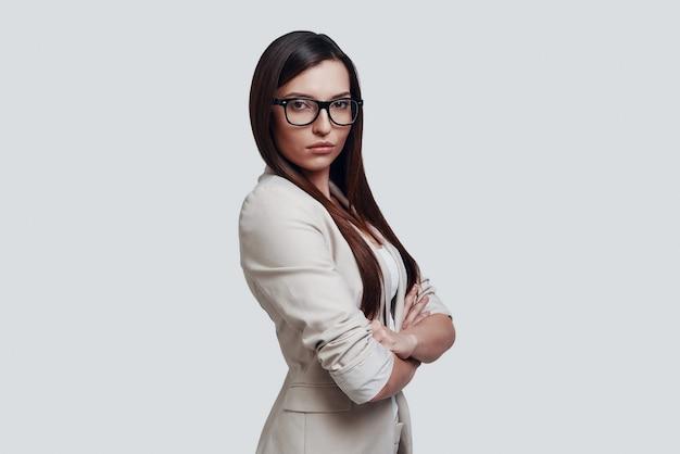 Serieuze vakkennis. aantrekkelijke jonge vrouw die naar de camera kijkt terwijl ze tegen een grijze achtergrond staat