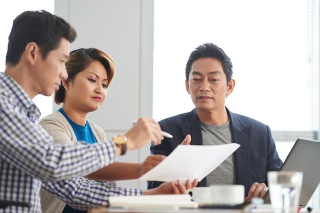 Serieuze volwassen ondernemer die collega's of zakenpartners vraagt om overeenkomst te ondertekenen na vergadering