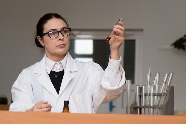 Serieuze vrouw in een witte jas arts medisch chemicus of bioloog werkt in het laboratorium