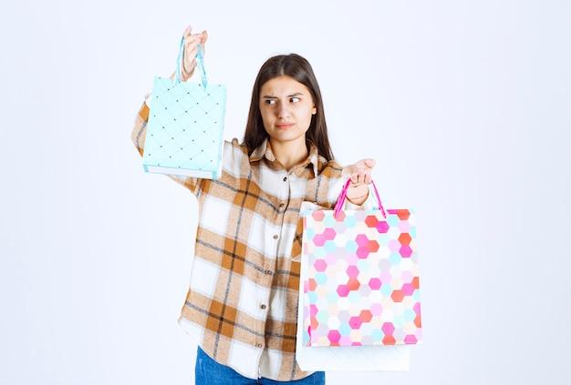 Serieuze vrouw kijkt naar een stel boodschappentassen over een witte muur.