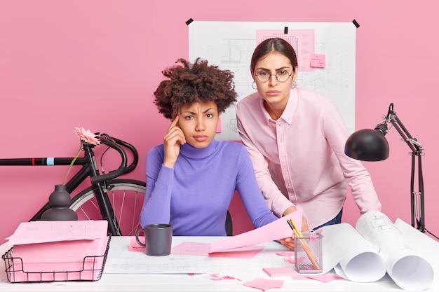 Serieuze vrouw van gemengd ras werkt samen aan een gemeenschappelijk project op kantoor, check documenten poseren op het bureaublad, werk samen en maak blauwdrukken