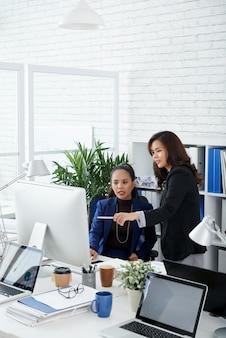 Serieuze vrouwelijke collega's die gegevens op het scherm van de computer bespreken en beslissen wat ze moeten doen om...