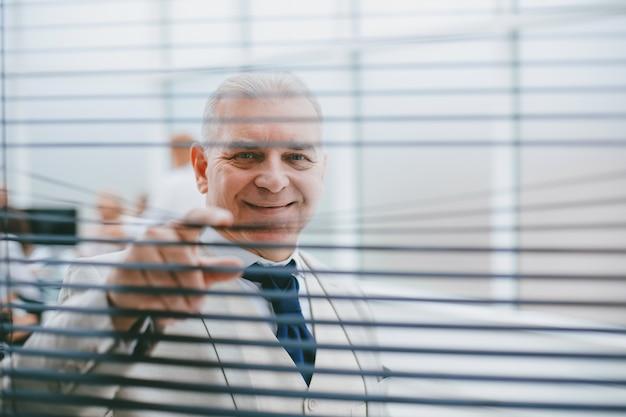 Serieuze zakenman die door de jaloezieën kijkt