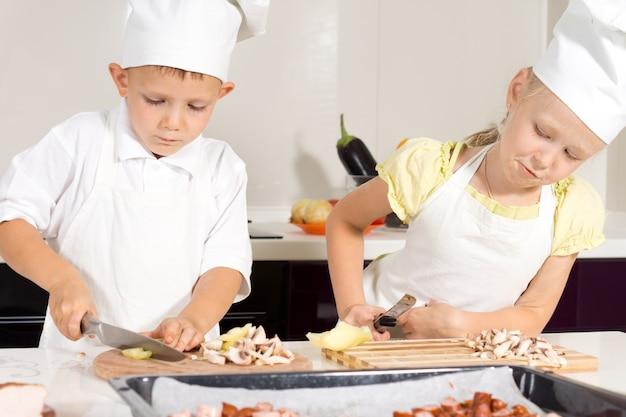Serious kid chefs snijden ingrediënten op houten snijplank in de keuken.