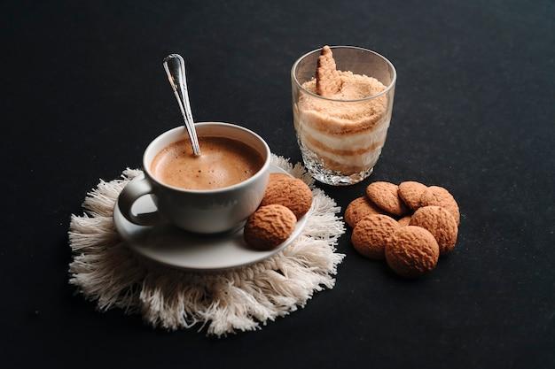 Serradura-dessert en hete koffie met wat koekjes en een donkere achtergrond