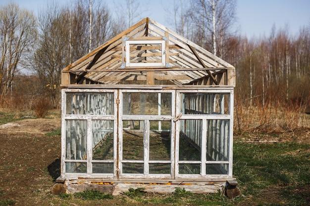 Serre uit de ramen in de tuin in het vroege voorjaar