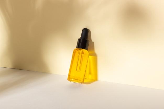 Serum en etherische cosmetische olie fles met druppelaar met schaduwen op de achtergrond. skincare beauty spa product en pipet
