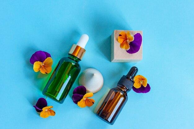 Serum glazen flessen met pipet en mooie altviool bloemen op blauwe achtergrond. natural organic spa cosmetisch concept. bovenaanzicht.