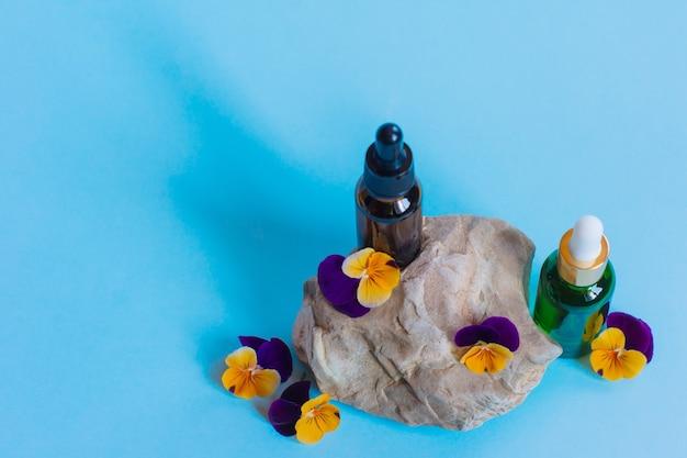 Serum glazen flessen met pipet en mooie altviool bloemen op blauwe achtergrond. natural organic spa cosmetisch concept. vooraanzicht.