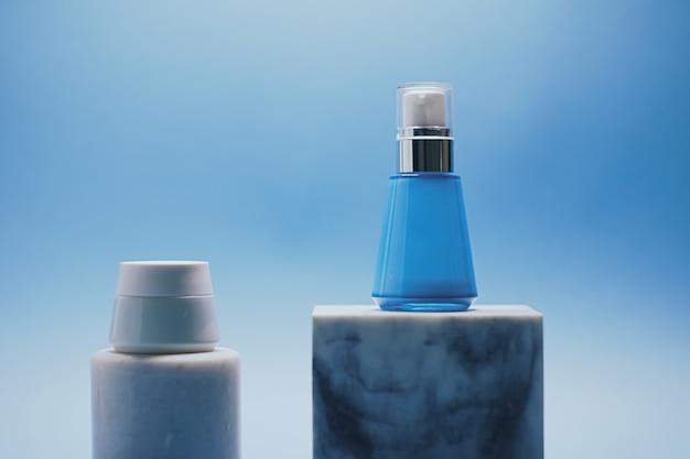 Serumfles en gezichtscrèmepot op blauwe achtergrond luxe huidverzorgingsproducten schoonheid en cosmetica
