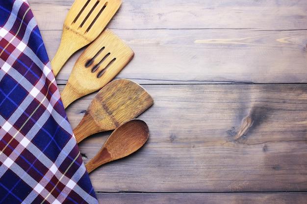 Serveerlepels op geruite doek liggend op houten oppervlak