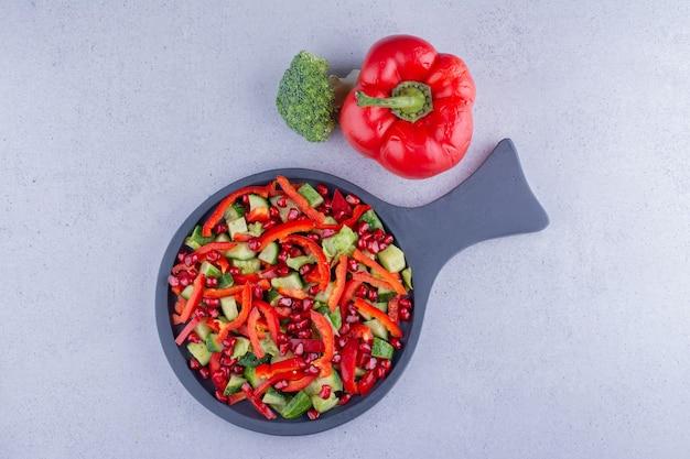 Serveerpan groentesalade naast een paprika en een broccoli op marmeren achtergrond. hoge kwaliteit foto