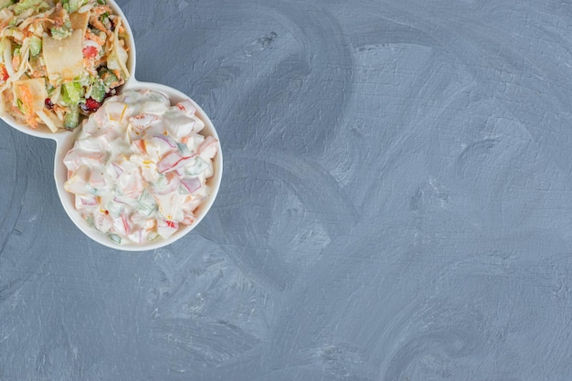 Serveerschotel met porties van olivier en gemengde groentesalades op marmeren tafel.