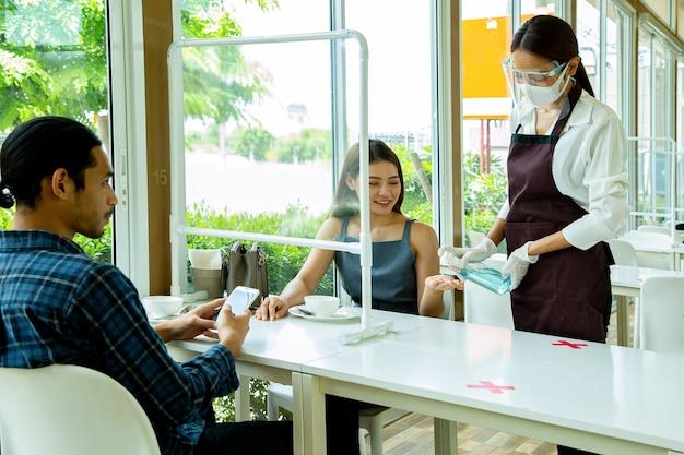 Serveerster die alcoholspray gebruikt voor hygiënische klanthand voordat ze apparatuur aanraakt of luncht in restaurant