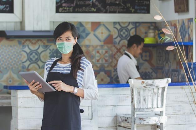 Serveerster die digitale tablet gebruikt en gezichtsmaskers draagt