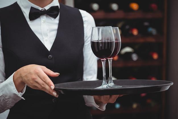 Serveerster die een dienblad met glazen rode wijn houdt