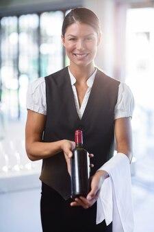 Serveerster die een fles rode wijn en een handdoek houdt