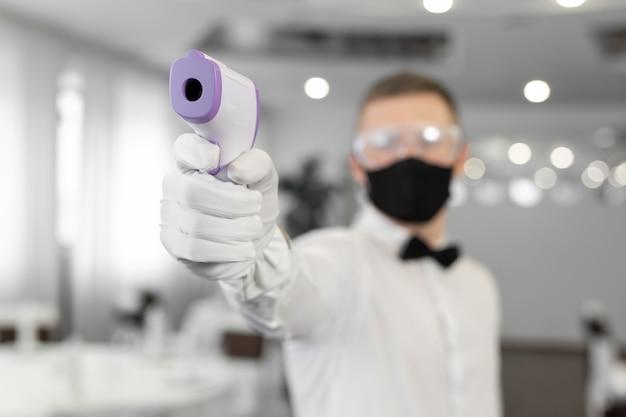 Serveerster die een gezichtsmasker draagt en een infraroodthermometer op haar voorhoofd houdt om de lichaamstemperatuur te controleren op symptomen van het virus bij klanten