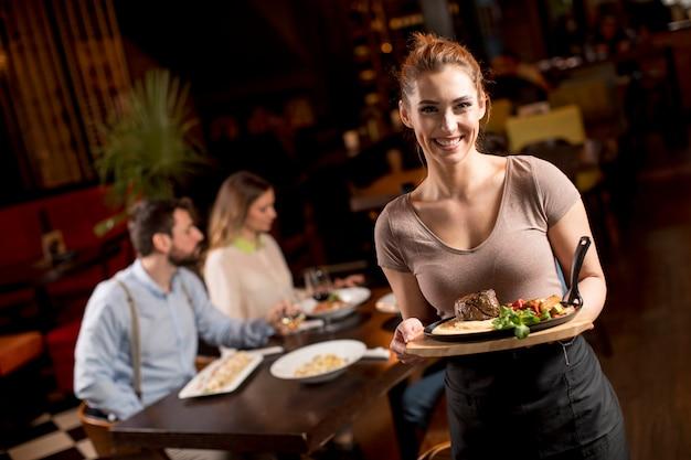 Serveerster die een houten plaat met biefstuk in het restaurant