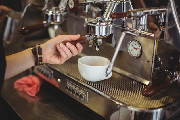 Serveerster die een kop koffie voorbereidt