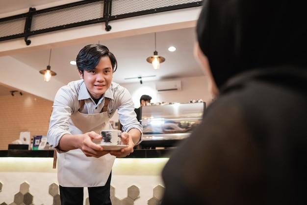 Serveerster die een kopje koffie aanbiedt voor de klant van het meisje in de coffeeshop